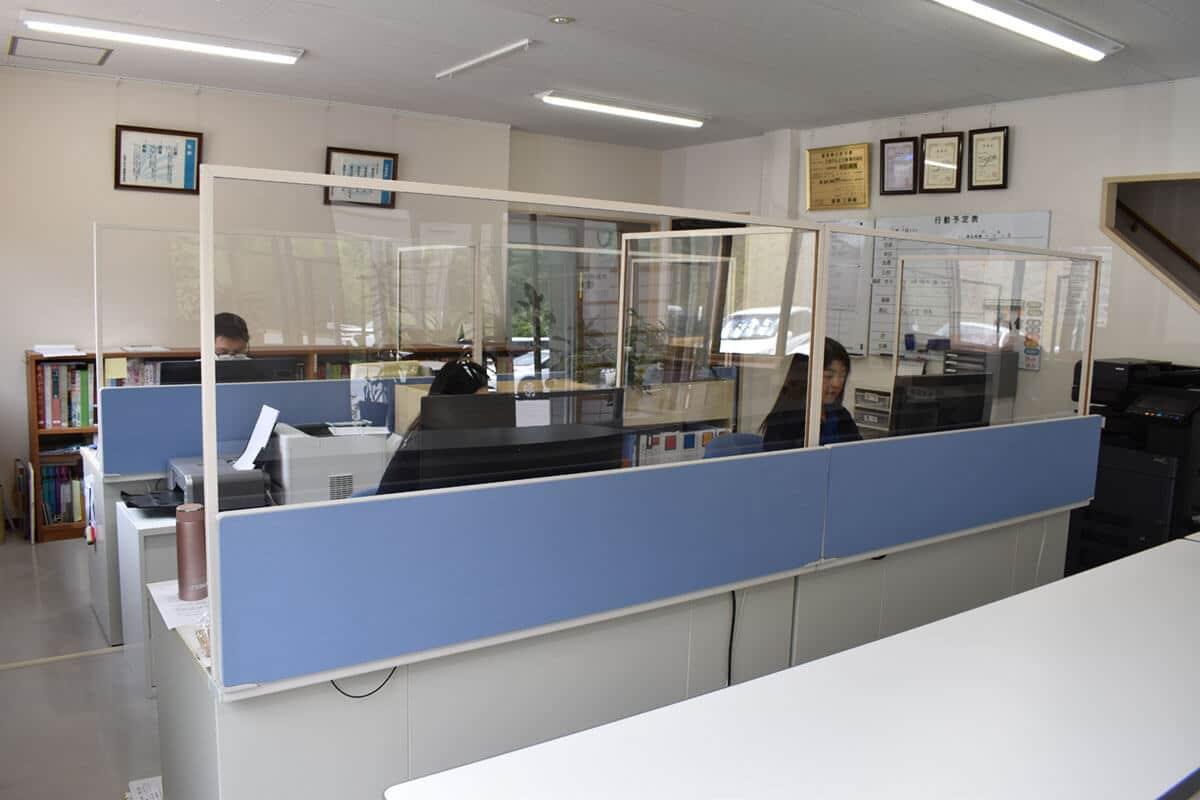 コロナ感染予防のパーティションで区切られた事務所
